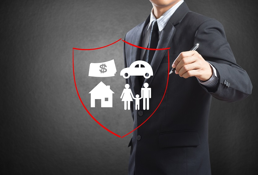 Business man drawing shield protecting family
